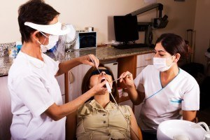 Dentist and assistant performing laser dental treatment on female patient.