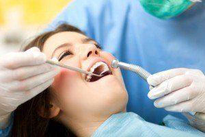Little girl smiling for dentist during wisdom teeth exam procedure.
