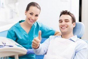 new patient giving thumbs up with dentist smiling.