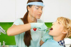 Dentist with masking preparing to do tooth extraction on a patient