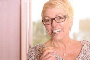 Close up Happy Middle Age Blond Woman, Wearing Eyeglasses, Biting a Fork While Looking at the Camera.